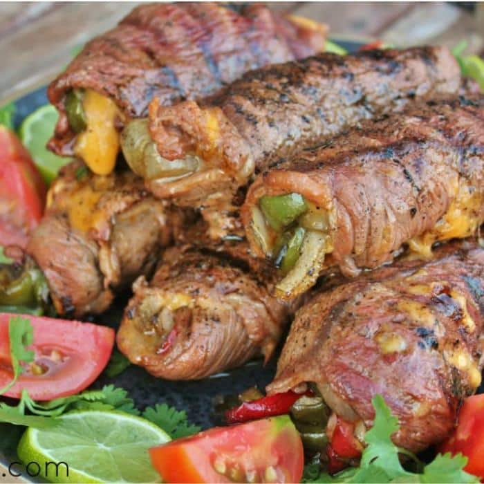 stacked cheesy steak fajita rolls next to sliced lemons and tomatoes