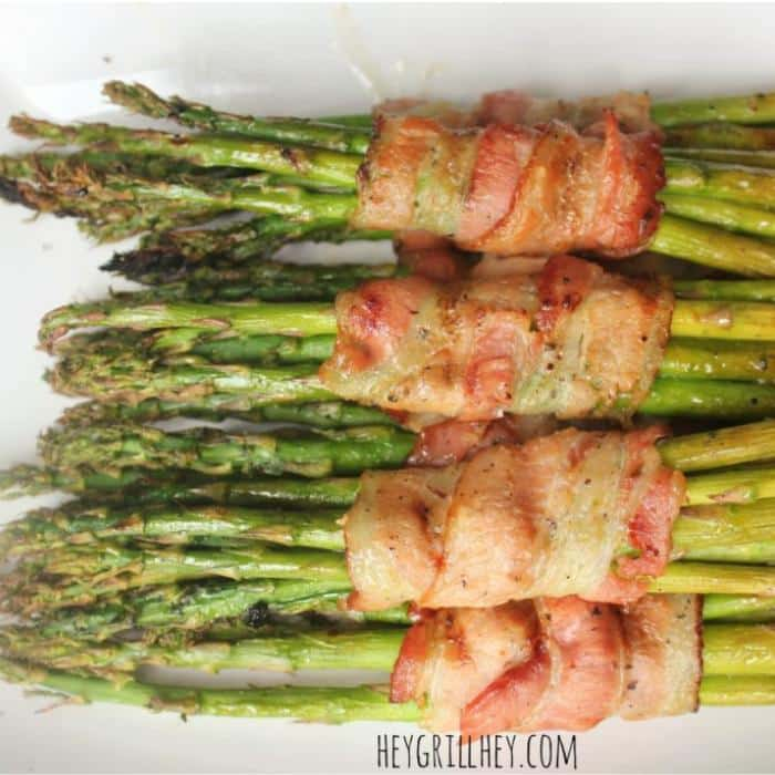 row of bacon wrapped asparagus on a white platter