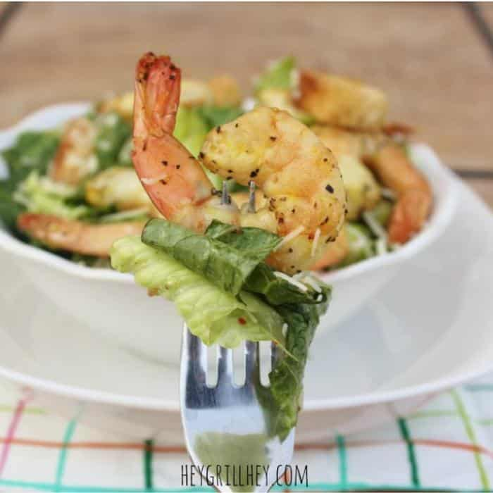 A bowl full of salad topped with shrimp