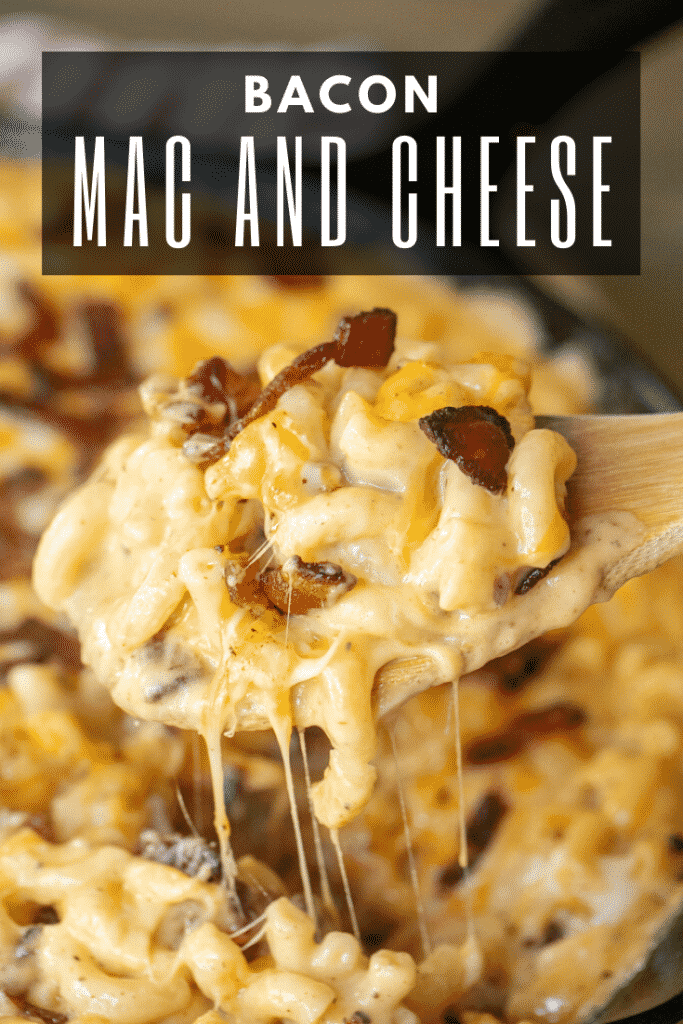 """Bacon mac and cheese being scooped out of a cast iron skillet with a wooden spoon. Text overlay: """"Bacon Mac and Cheese"""""""