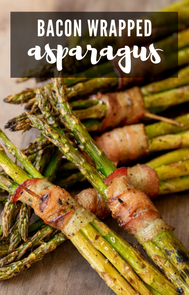 Asparagus clusters wrapped in bacon on top of a wooden cutting board