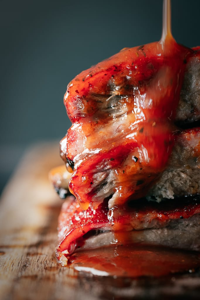 BBQ sauce drizzling down a stack of sliced hot and fast ribs.