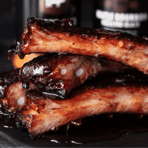 Sauced and smoked ribs stacked in front of bottles of BBQ sauce.
