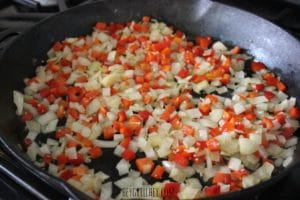 close up shot of frying pan full of chopped white onions and chopped red bell peppers