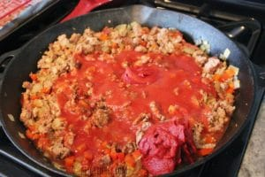 Cooked ground turkey in pan on stovetop with red sauce on top
