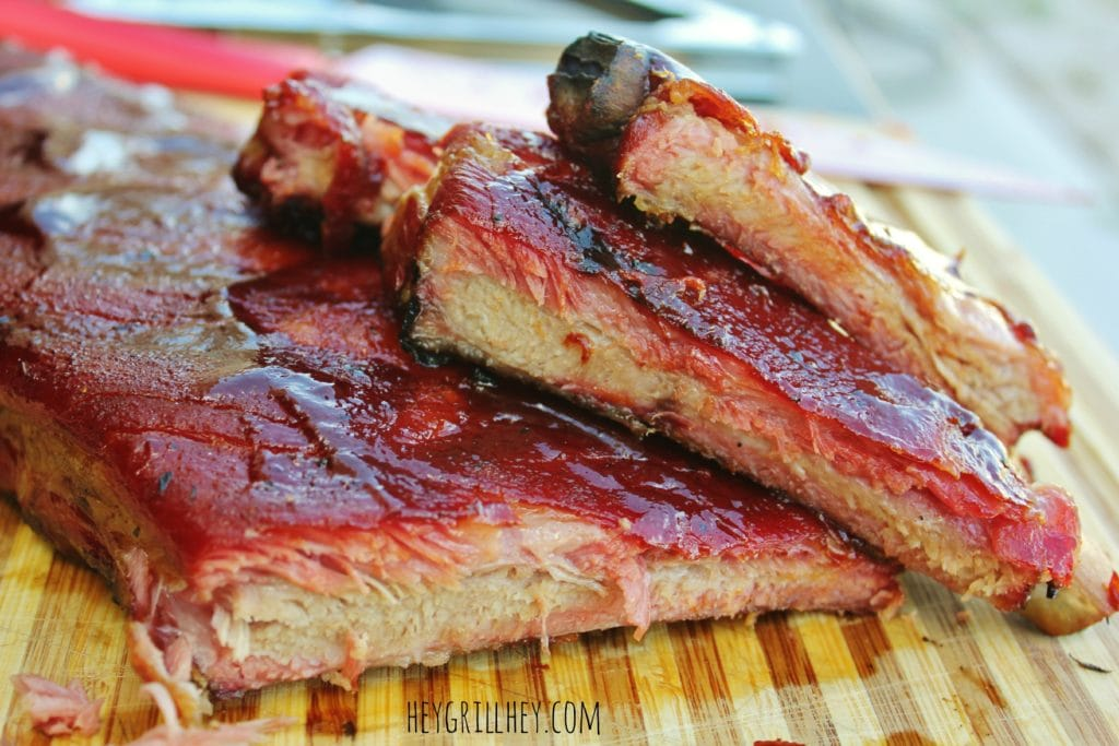 Cooked ribs sliced and stacked on a wooden cutting board