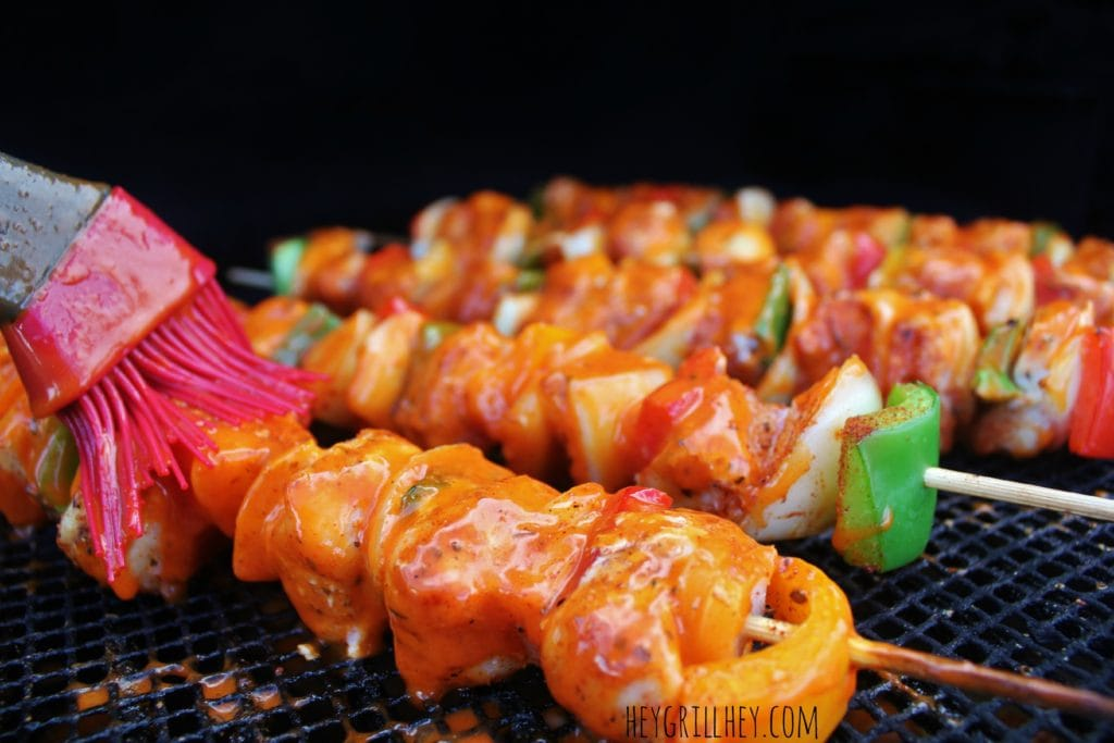 Close up shot of cooked and cubed chicken and peppers on the grill grate being brushed with buffalo Sauce.