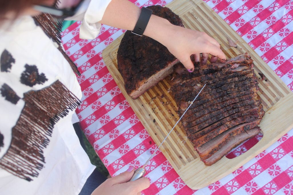 overhead view of a sliced brisket on a wooden cutting board.
