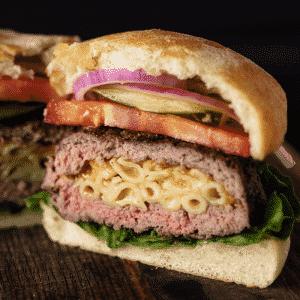 Mac and cheese stuffed hamburger sliced in half.