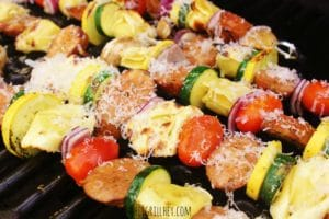 metal skewers filled with alternating chopped and uncooked pieces of mushroom, purple onion, tortellini pasta, sausage, yellow squash, zucchini, and cherry tomato, all arranged in a line on the grill grate inside the grill and topped with grated parmesan cheese