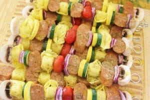 metal skewers filled with alternating chopped, seasoned, and uncooked pieces of mushroom, purple onion, tortellini pasta, sausage, yellow squash, zucchini, and cherry tomato, all arranged in a line on a wooden cutting board