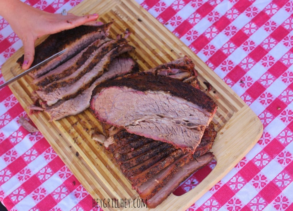 Brisket point being sliced on a wood cutting board.