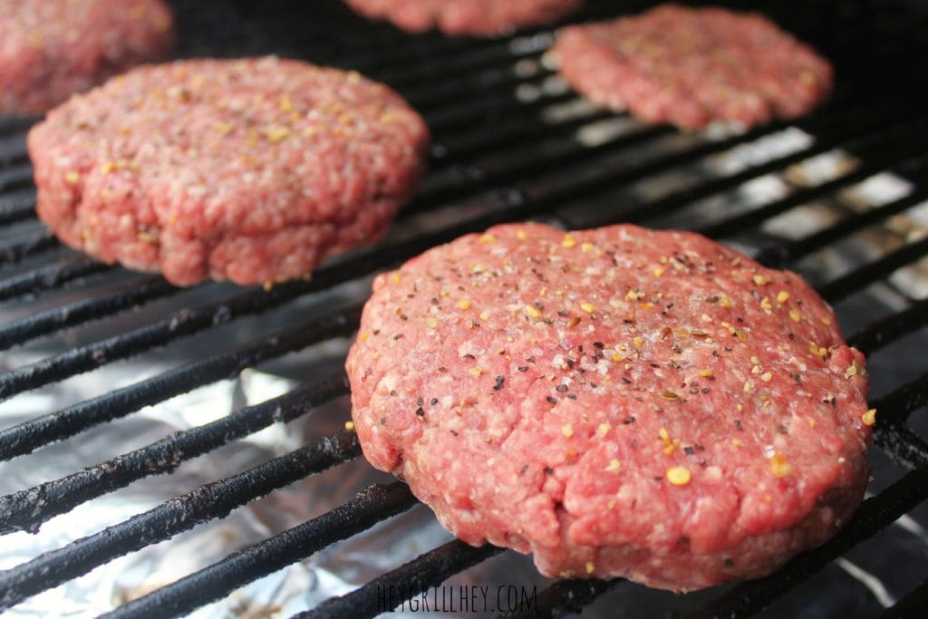 Uncooked hamburger patties on the grill grate.