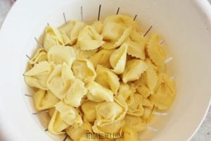 Uncooked tortellini noodles in a white slatted bowl