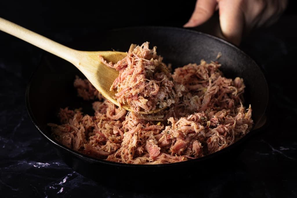 Shredded pulled pork on a wooden spoon above a cast iron skillet full of shredded pork.