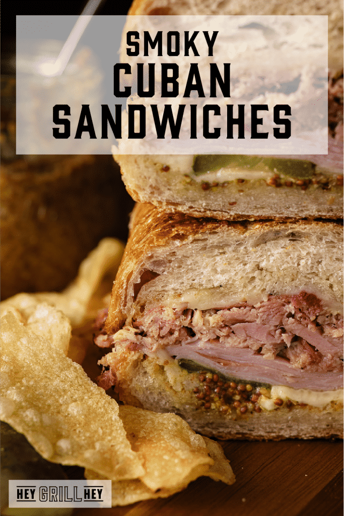 Two Cuban sandwiches stacked on a wooden board next to potato chips with text overlay - Smoky Cuban Sandwiches.