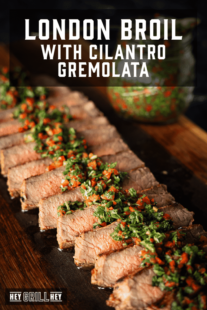 Sliced London broil lined up on a wooden cutting board topped with cilantro gremolata with text overlay - London Broil with Cilantro Gremolata.