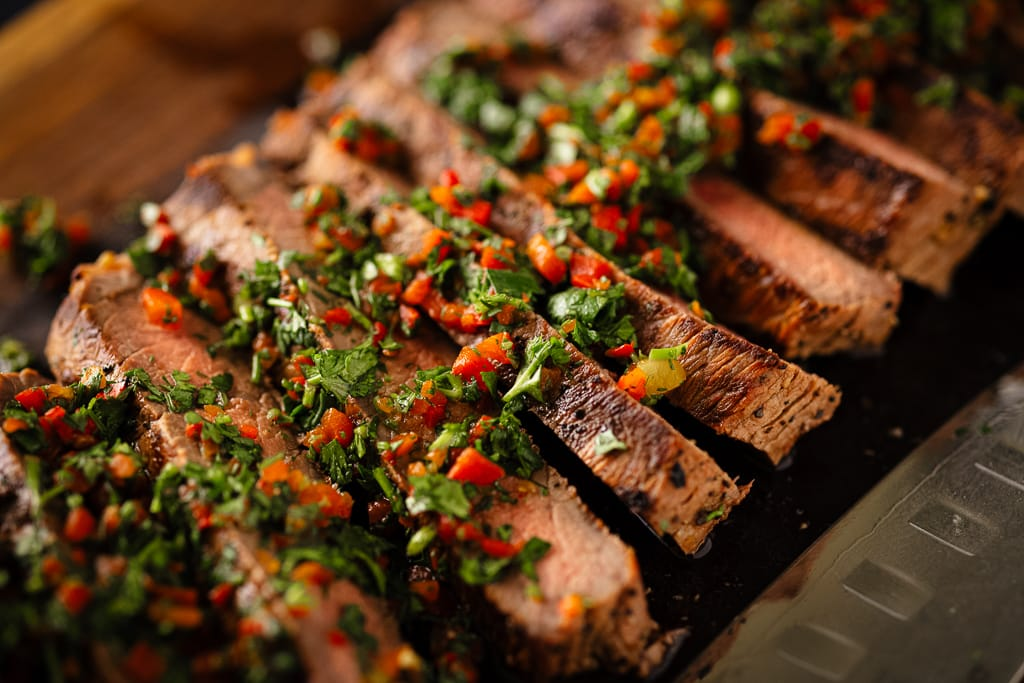 Sliced London broil on a wooden cutting board topped with cilantro gremolata.