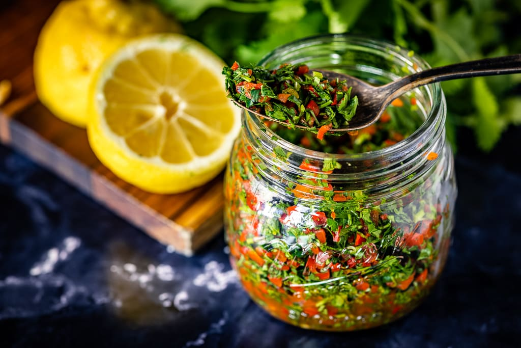 Cilantro gremolata in a small glass mason jar with sliced lemons in the baground.