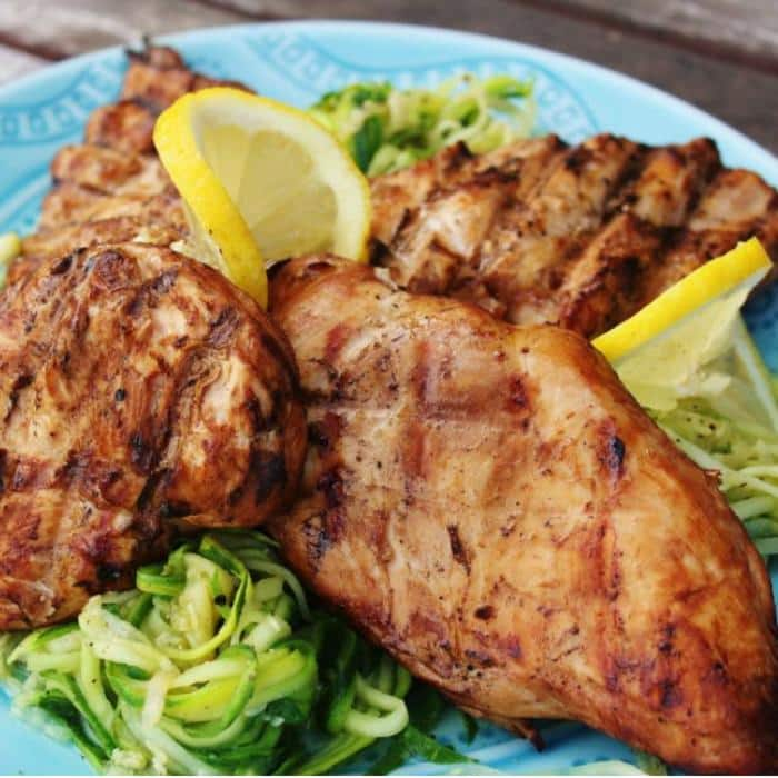 skinny grilled lemon chicken on a plate with lemon slices
