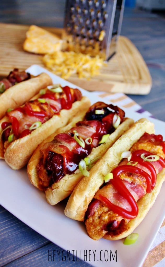 5 recipes for the best stuffed hot dogs ever on a white plate with grated cheese in the background