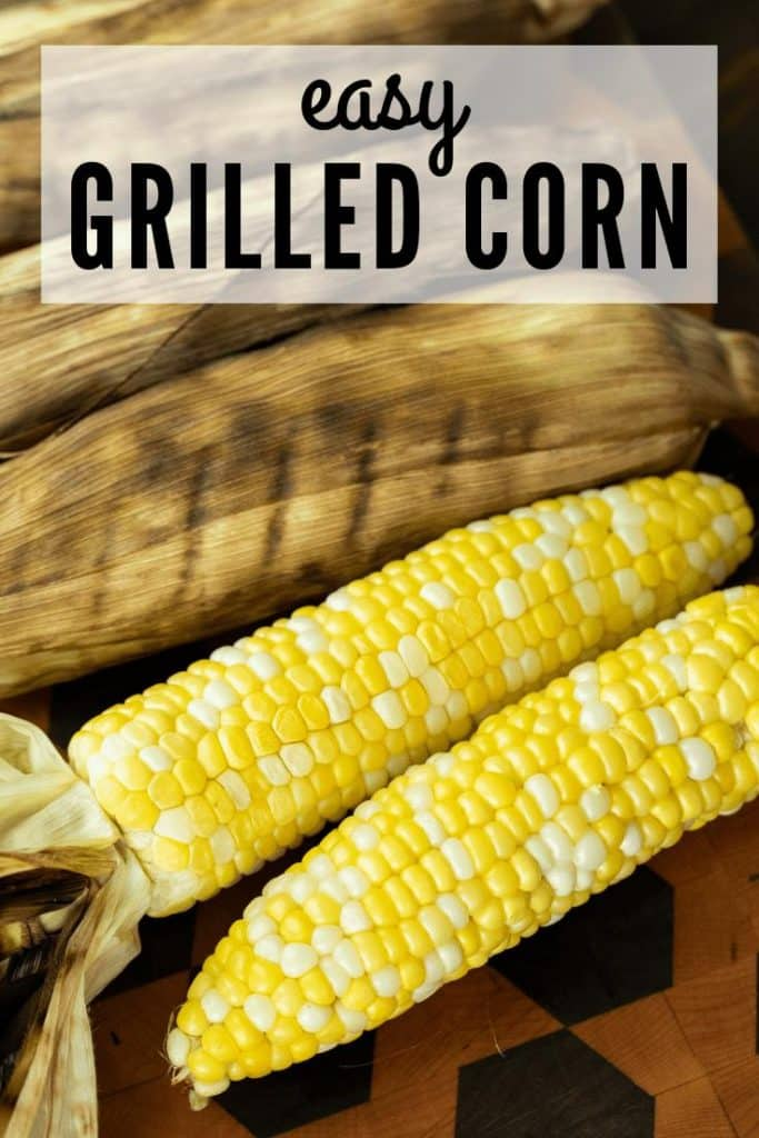 grilled corn in the husk and shucked grilled corn on a wooden cutting board