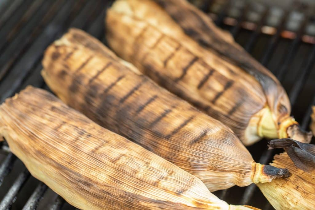 3 corn on the cob in husks on the grill
