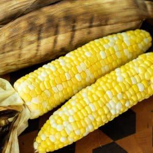 Two corn on the cob on a wood cutting board