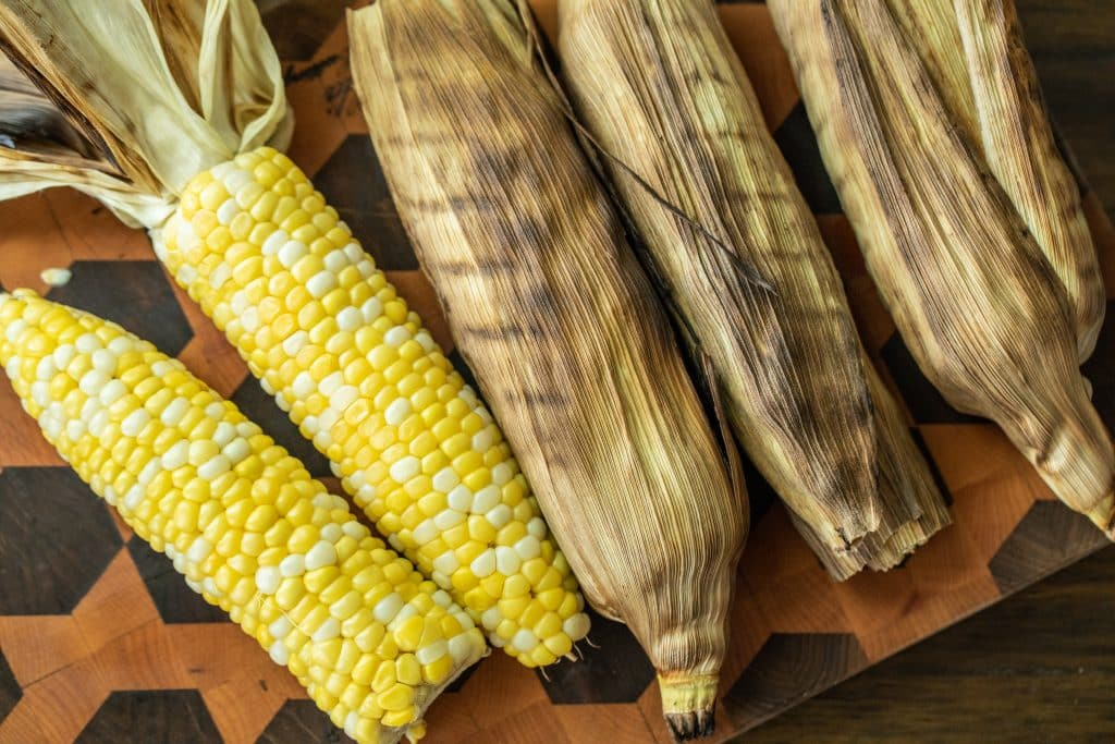 grilled corn in the husk and peeled grilled corn on a wooden cutting board