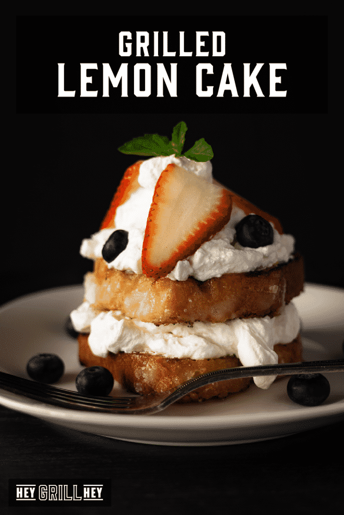 Grilled lemon cake topped with whipped cream and fresh blueberries and strawberries with text overlay - Grilled Lemon Cake.