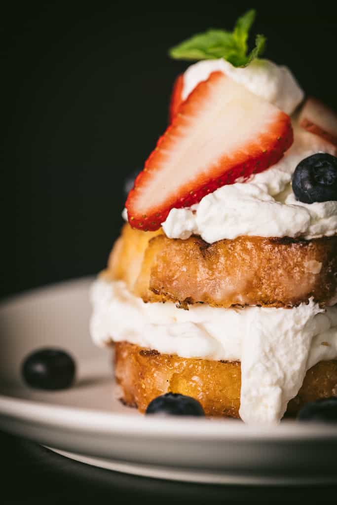 Grilled lemon cake topped with whipped cream and fresh blueberries and strawberries on a white plate.