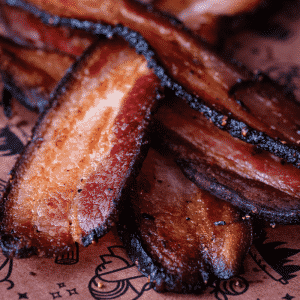 Stack of homemade smoked bacon slices on peach butcher paper.