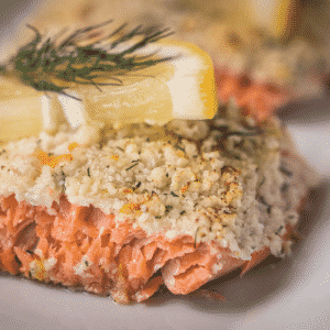 Parmesan crusted salmon garnished with lemon slices and dill.