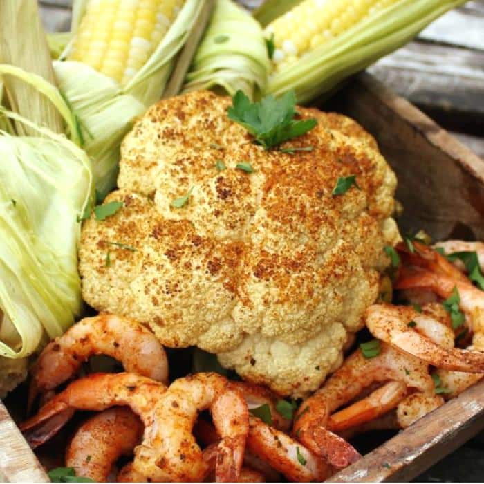 whole grilled cauliflower next to grilled shrimp and corn