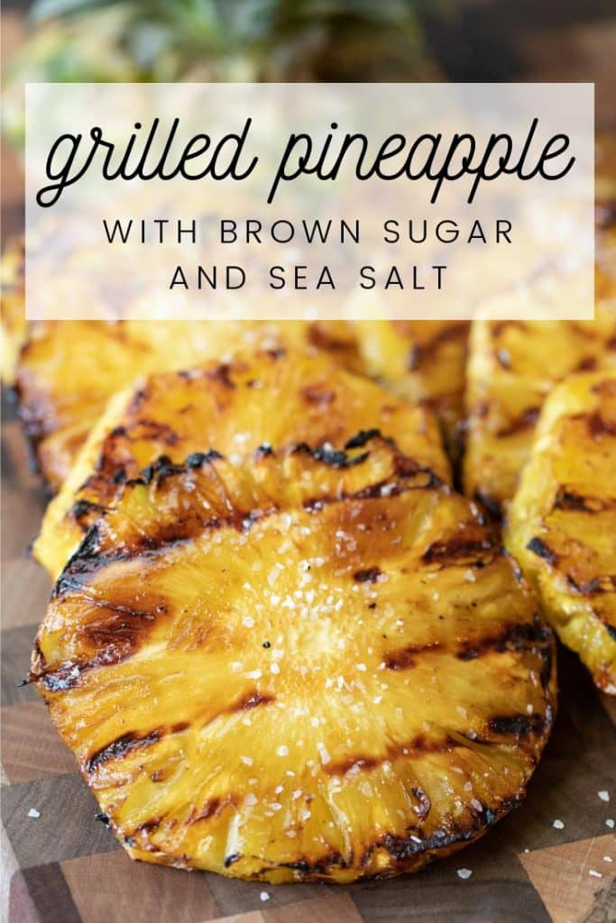 Grilled pineapple with dark grill marks on a wood cutting board.