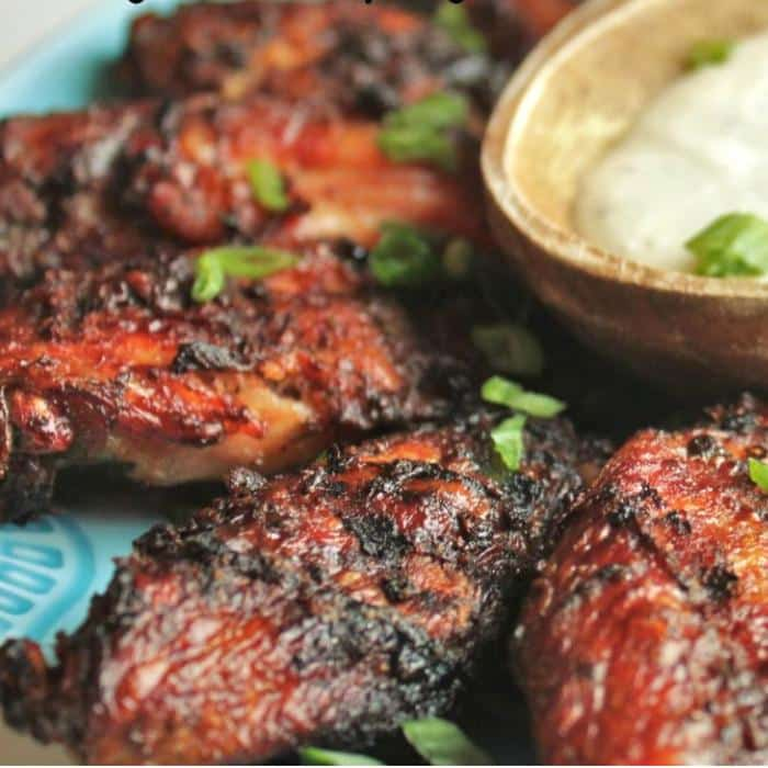 smoked jerk chicken wings next to a bowl of dipping sauce