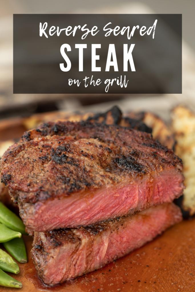Reverse seared steak, cut in half to see medium rare inside, on a wood plate.