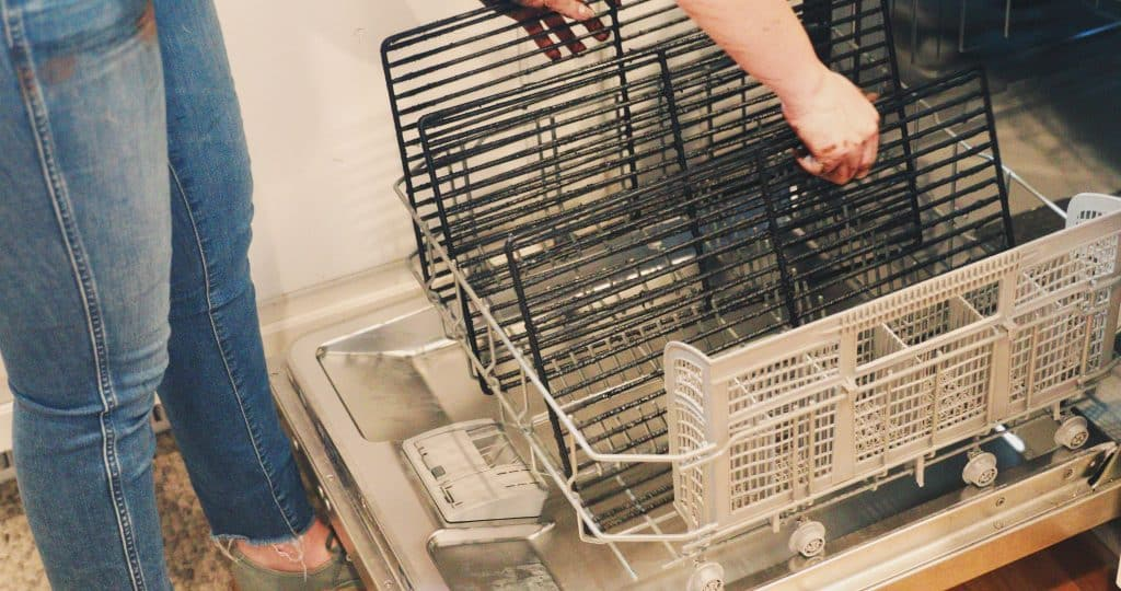 Woman placing grill grates in a dishwasher.