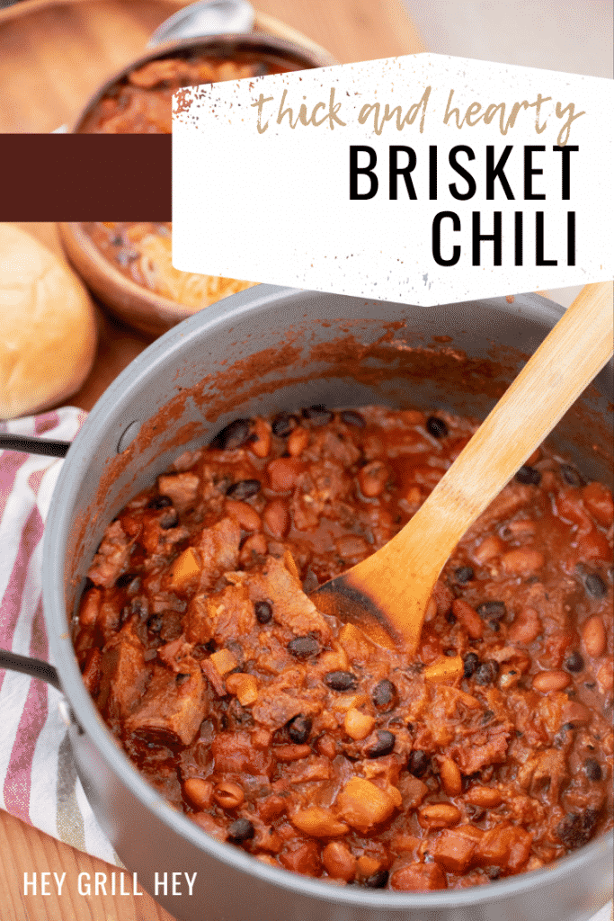 Gray pot full of brisket chili with a bowl of brisket chili and a roll in the background. Text overlay reads: Thick and Hearty Brisket Chili.