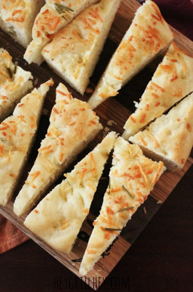 Homemade Rosemary Parmesan Focaccia sliced in to triangle shaped pieces and served on a wooden cutting board.