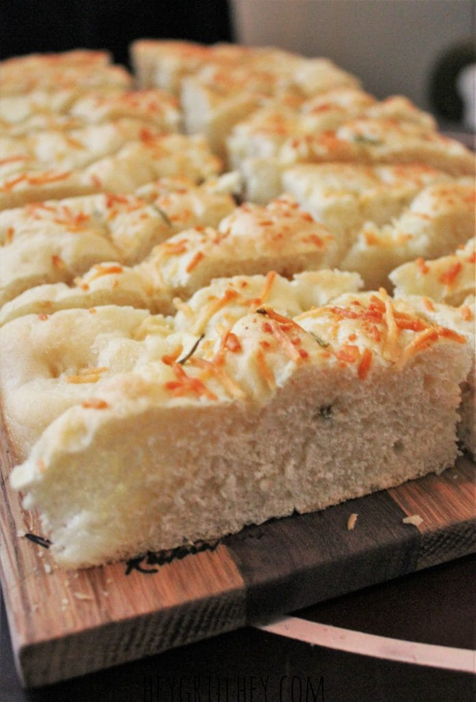 Rosemary Parmesan Focaccia bread, sliced and served on a wooden cutting board.