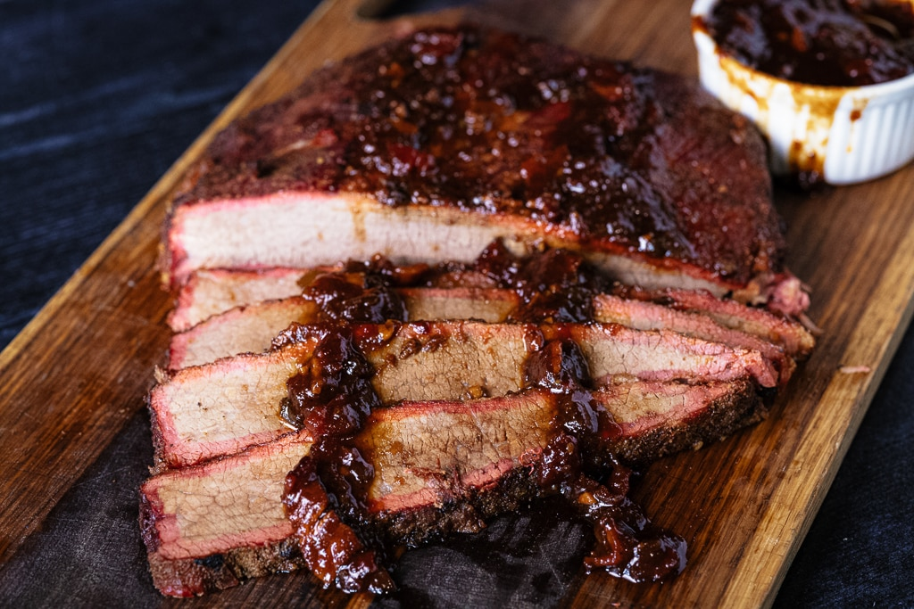 Sliced brisket on a cutting board drizzled with bacon BBQ sauce.