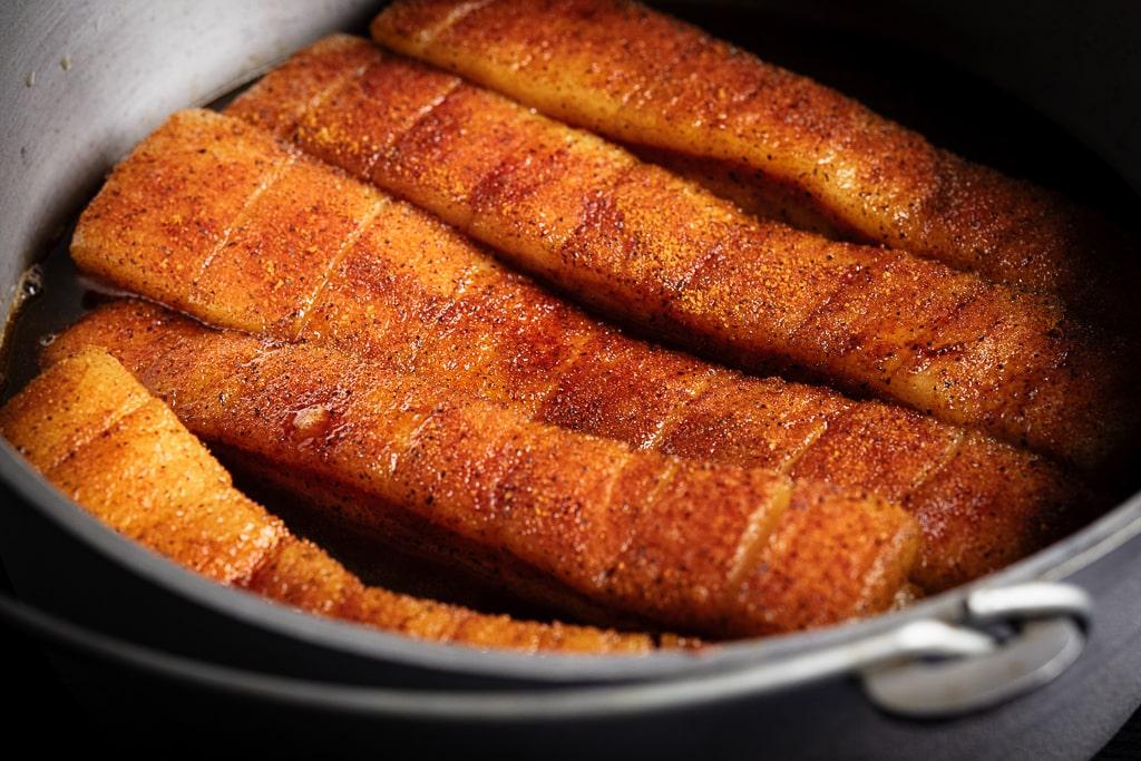 Seasoned pork belly in a large Dutch oven.