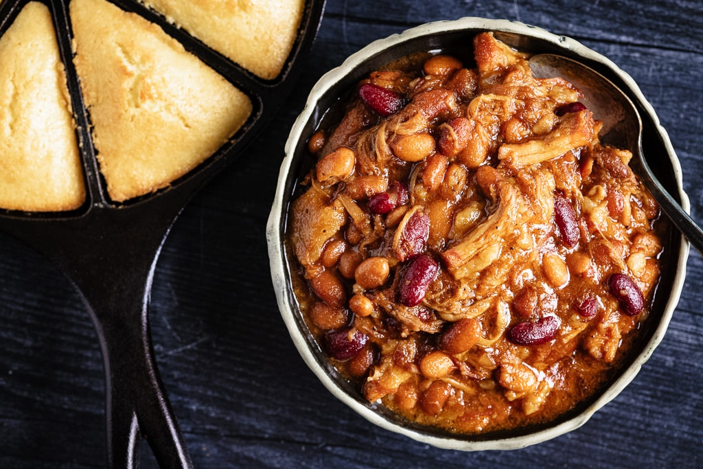Bowl of pork belly bourbon baked beans in a bowl next to a skillet of corn bread.