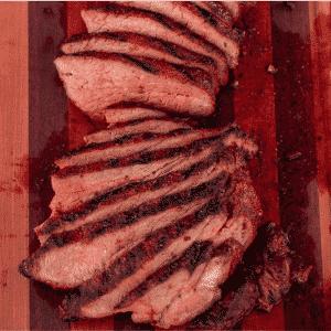 Sliced coffee rub tri tip on a striped wooden cutting board.