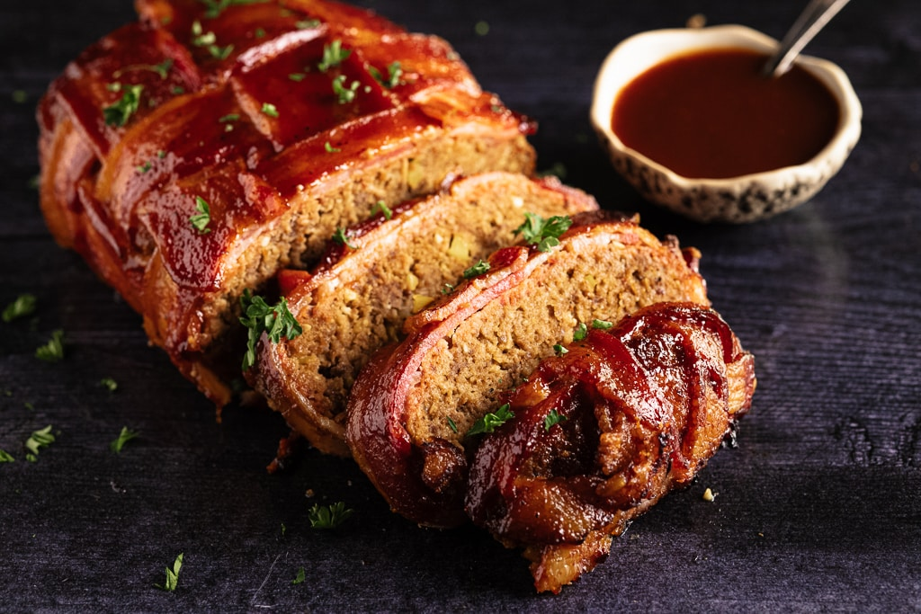 Sliced bacon weave wrapped meatloaf next to a bowl of BBQ sauce.