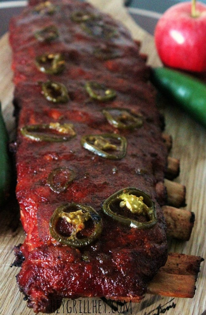 Rack of Apple Jalapeno pork ribs resting on a wooden cutting board.