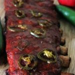 Rack of smoked ribs topped with sliced jalapenos.
