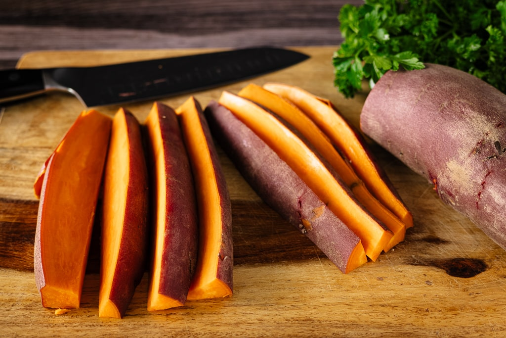 Sliced sweet potato spears on a wooden cutting board with a knife on the board in the background.