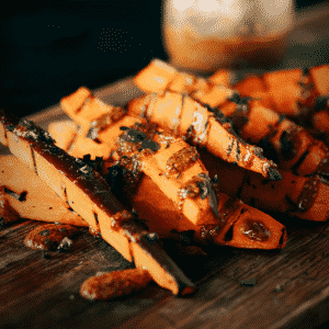 Grilled sweet potato fries drizzled with honey mustard sauce on a wooden cutting board.